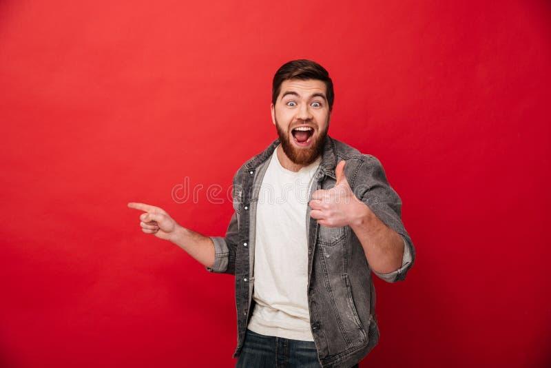 Opgetogen donkerbruine mens in toevallige clothin die duim tonen terwijl royalty-vrije stock afbeeldingen