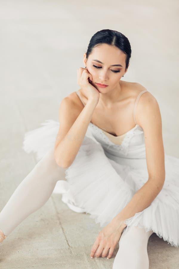 Opgetogen en ernstige ballerinazitting op de vloer stock afbeelding