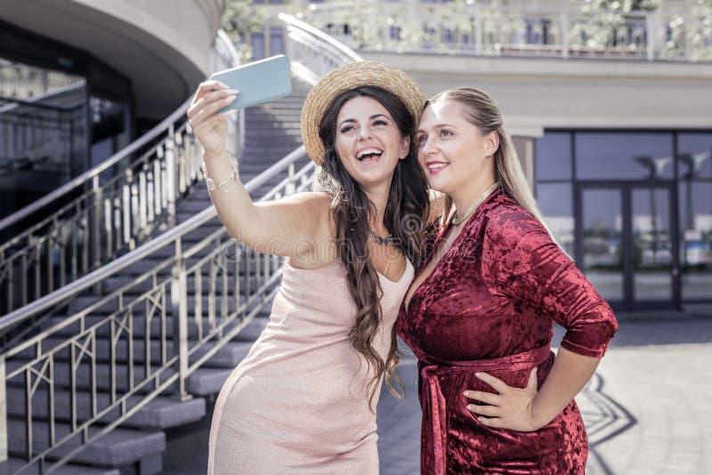 Opgetogen gelukkige vrouwen die een selfie samen nemen royalty-vrije stock foto's