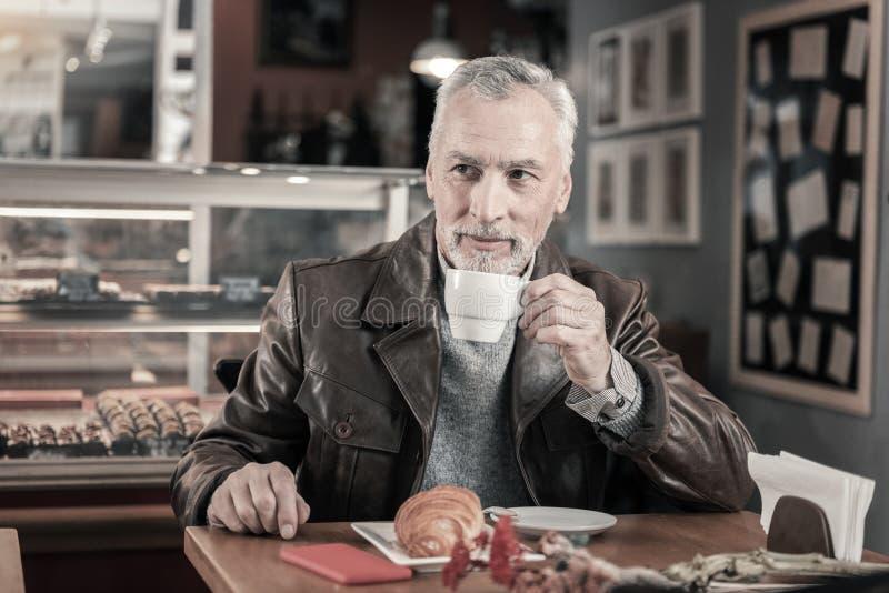 Opgetogen grijs-haired mens die aroma van koffie genieten royalty-vrije stock afbeelding