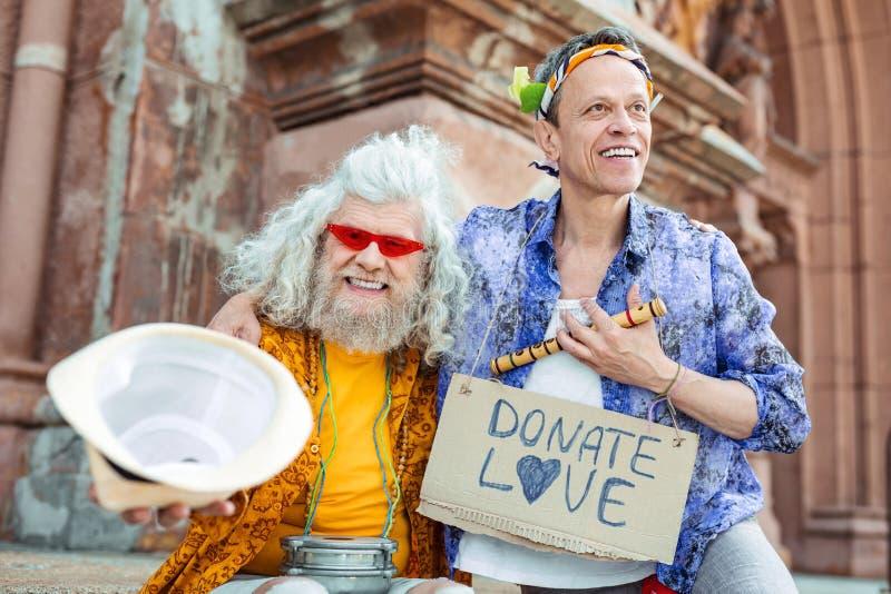 Opgetogen hippies die vrolijk na straatmuziek voelen royalty-vrije stock afbeelding