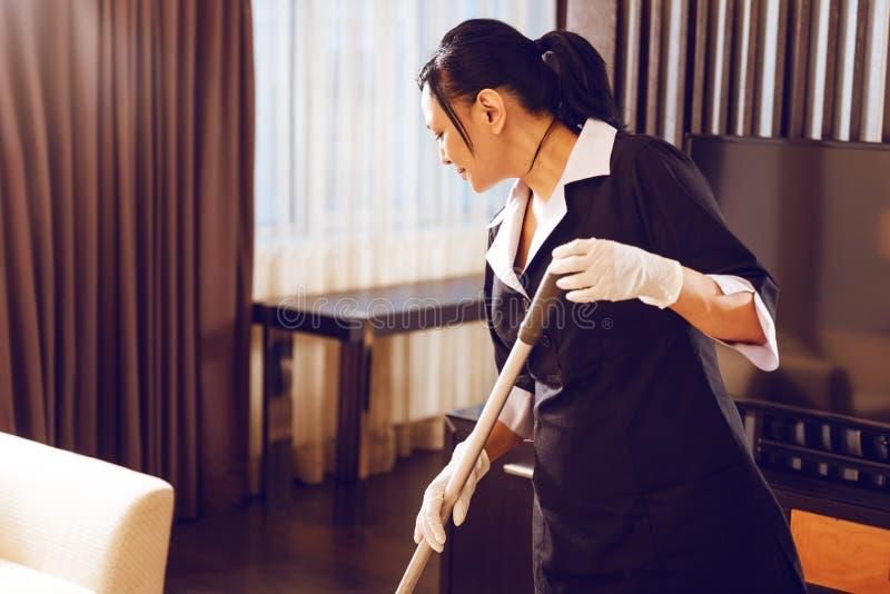Opgetogen hotelarbeider die zich in semi positie bevinden stock foto's