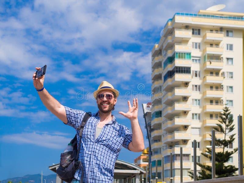 Opgetogen jonge mens in in geruite overhemd het besteden tijd openlucht, onderzoekend de omgeving in ochtend Glimlachende Kerel royalty-vrije stock fotografie