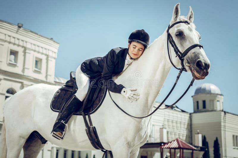Opgetogen jonge vrouw die haar wit paard koesteren stock fotografie