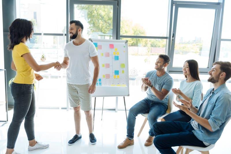Opgetogen jongeren die een teambuilding activiteit doen royalty-vrije stock afbeelding