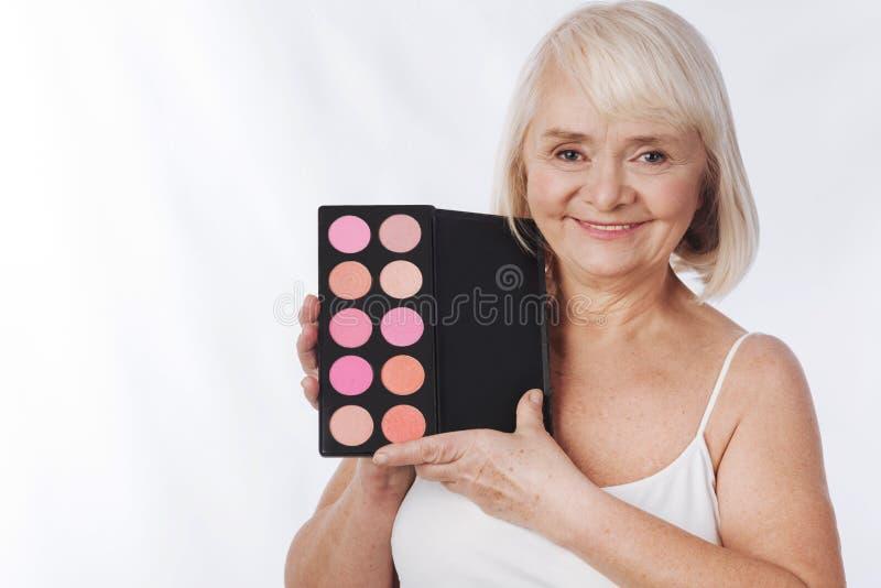 Opgetogen knappe vrouw die een rougepalet houden royalty-vrije stock foto's