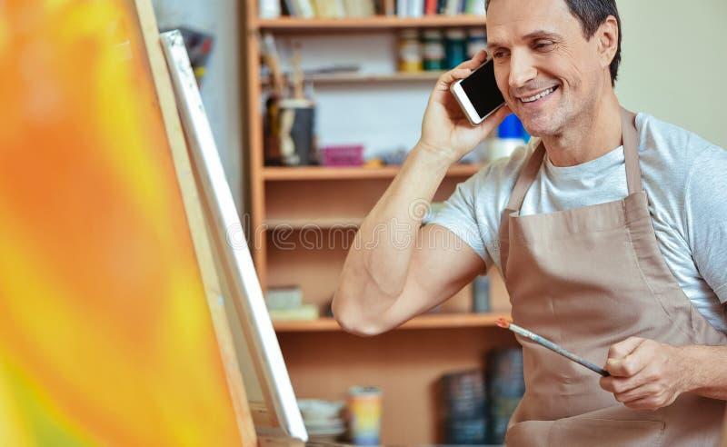 Opgetogen kunstenaar die cellphone in het schilderen van studio gebruiken stock afbeelding