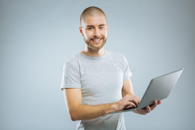 Opgetogen mannelijke persoon die zijn computer met behulp van stock foto