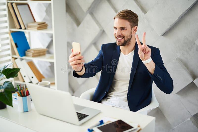 Opgetogen mens die online in bureau communiceren stock afbeelding