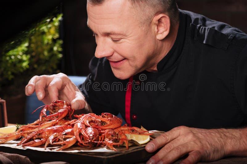 Opgetogen mens die rivierkreeften in restaurant eten royalty-vrije stock foto