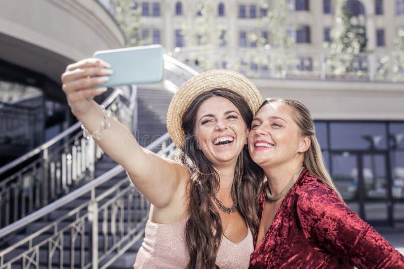 Opgetogen positieve jonge vrouwen die foto's samen nemen royalty-vrije stock fotografie