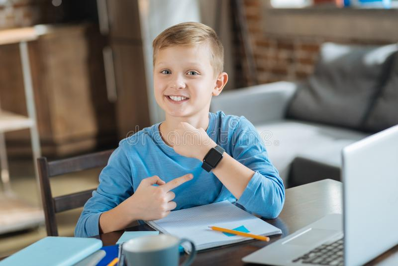 Opgetogen positieve jongen die op zijn smartwatch richten stock afbeelding