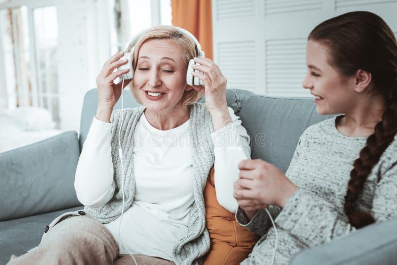 Opgetogen positieve oude vrouw die haar hoofdtelefoons houden stock foto's