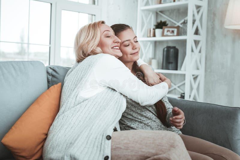 Opgetogen positieve oude vrouw die haar kleindochter koesteren stock afbeeldingen