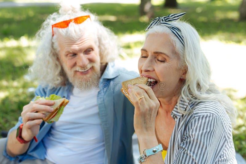 Opgetogen positieve vrouw die een sandwich bijten royalty-vrije stock afbeelding