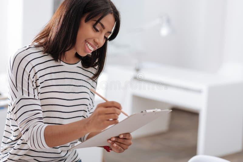 Opgetogen prettige vrouw die in haar nota's schrijven stock afbeeldingen