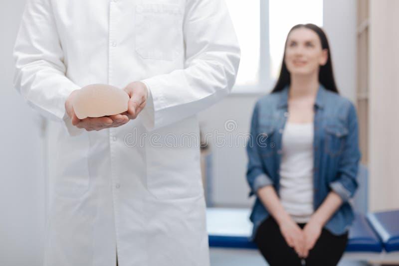 Opgetogen prominente arts die een bezoek van jonge dame ontvangen stock afbeelding