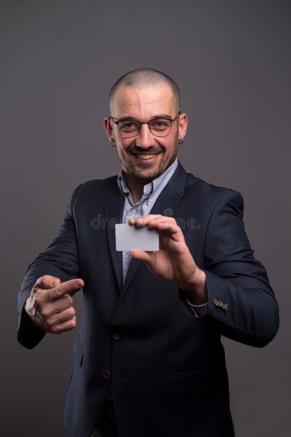 Opgetogen zakenman die die een creditcard tonen op grijze achtergrond wordt geïsoleerd stock afbeelding