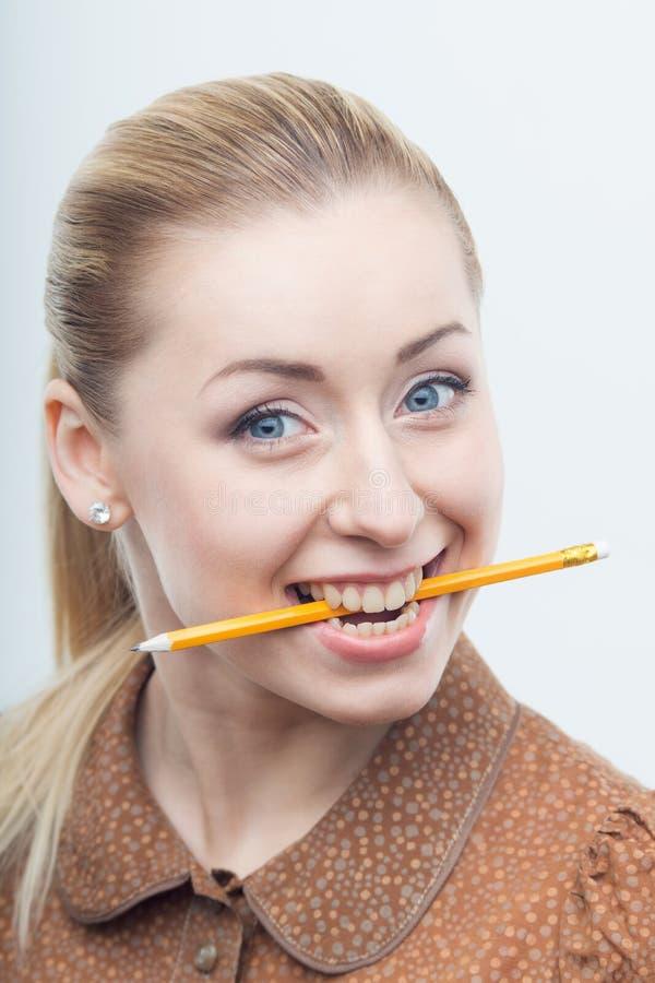 Opgewekt aantrekkelijk vrouw het bijten potlood royalty-vrije stock afbeelding