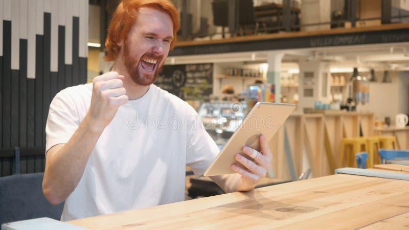 Opgewekt de Mens van de Roodharigebaard het Vieren Succes op Tablet royalty-vrije stock fotografie
