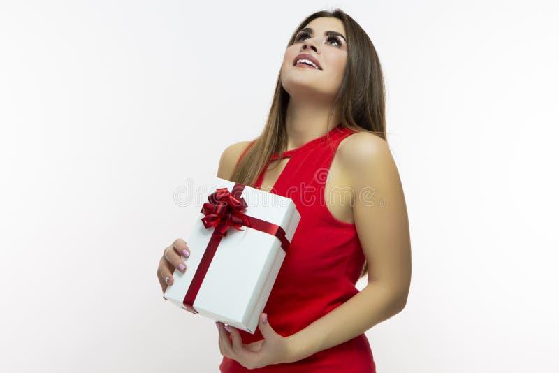 Opgewekt en Glimlachend Kaukasisch Meisje in Rode Kleding en Santa Hat Openend Witte die Giftdoos omhoog met rood Lint wordt verp royalty-vrije stock afbeeldingen