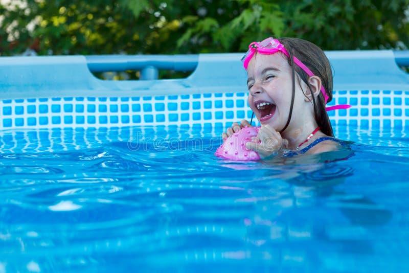 Opgewekt gelukkig meisje in zwembad royalty-vrije stock afbeeldingen