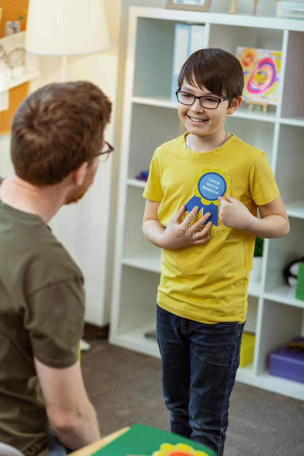 Opgewekt gelukkig weinig jongen die funky beloning voor zijn kennis krijgen stock afbeelding