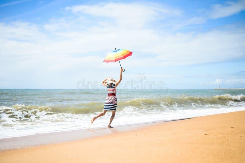 Opgewekt gelukkig wijfje die pret op strandgang hebben op zonnige in openlucht achtergrond stock foto's