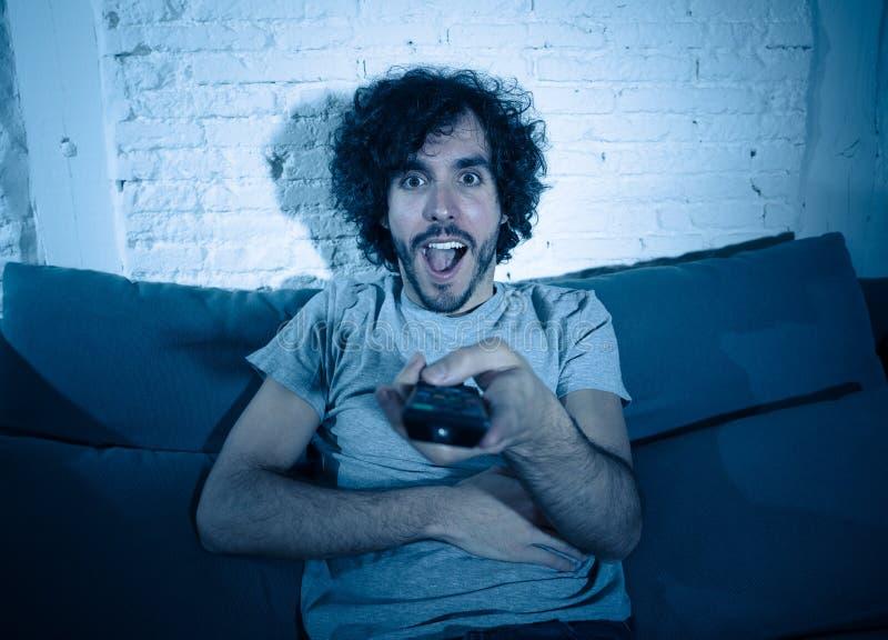 Opgewekt jong de mens van de sportenventilator het letten op voetbalspel op televisie, het vieren doel en het gillen royalty-vrije stock foto
