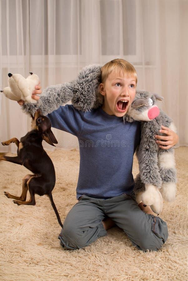 Opgewekt jong geitje met een stuk speelgoed en een hond op het tapijt stock foto