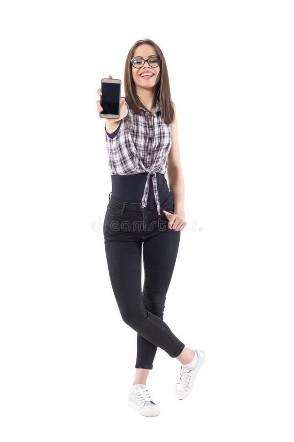 Opgewekt jong lachend modieus meisje die lege cellphonevertoning tonen bij camera stock foto