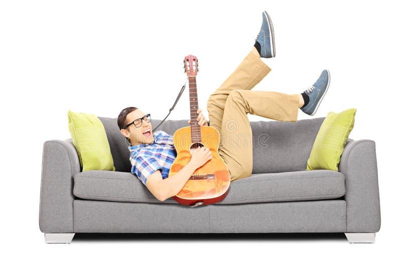 Opgewekt jong mannetje die op een bank liggen en een gitaar spelen royalty-vrije stock foto's