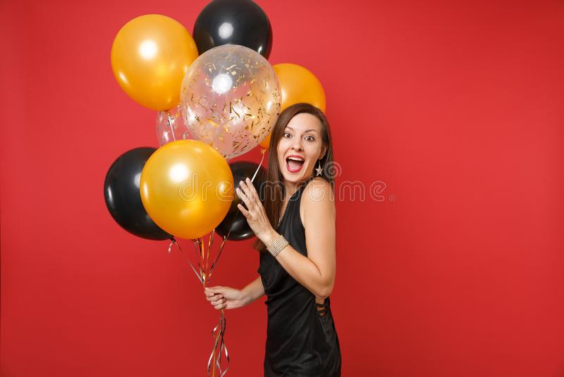 Opgewekt jong meisje in weinig de zwarte kleding het vieren ballons van de holdingslucht geïsoleerd op rode achtergrond St Valent royalty-vrije stock afbeeldingen