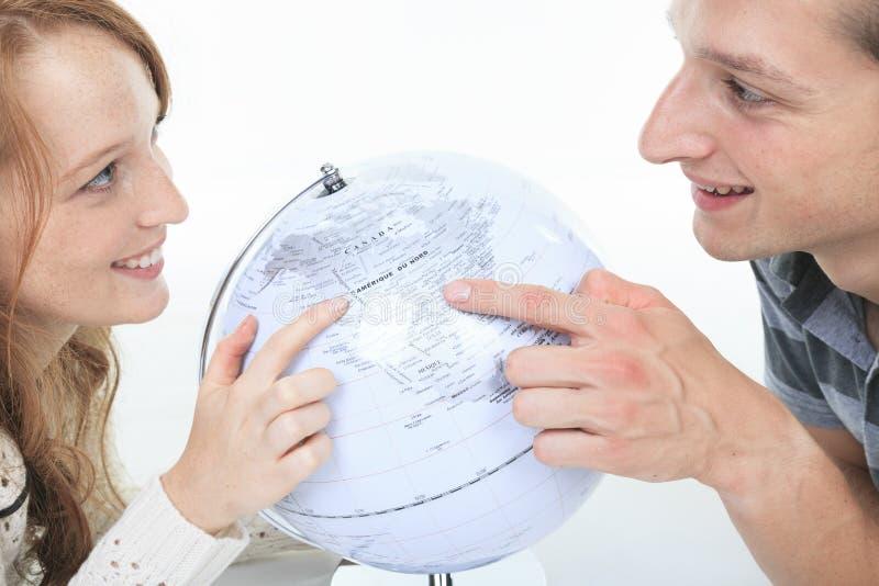 Opgewekt jong paar die hun vakantie plannen stock afbeelding