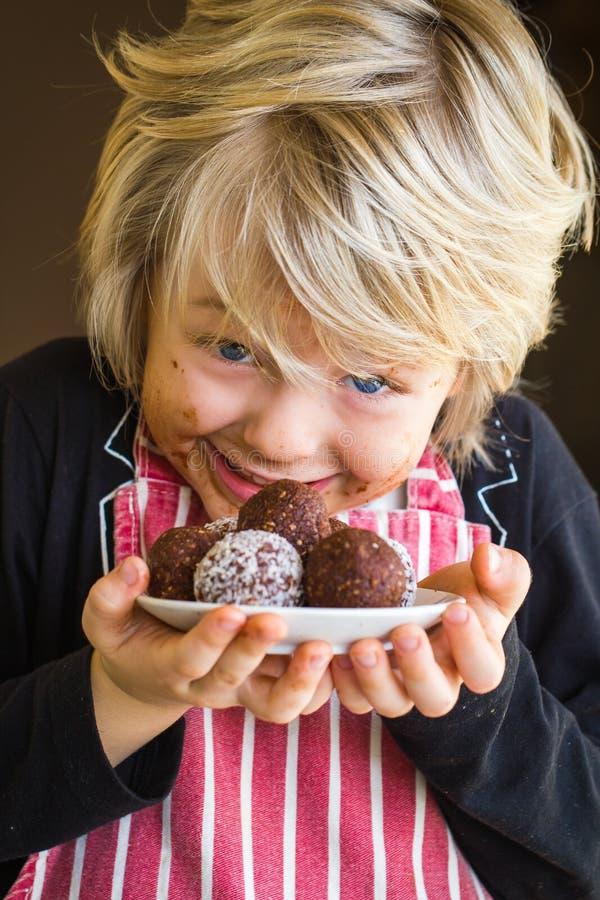 Opgewekt kind die eigengemaakte chocoladeballen tonen royalty-vrije stock foto