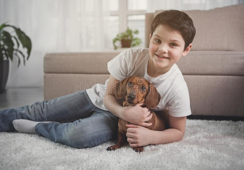 Opgewekt kind die zijn favoriet binnenlands huisdier omhelzen stock afbeelding