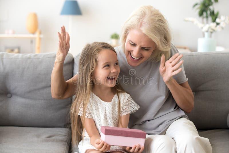 Opgewekt kleinkind gelukkig om verjaardagsgeschenk te ontvangen van het houden van stock foto's