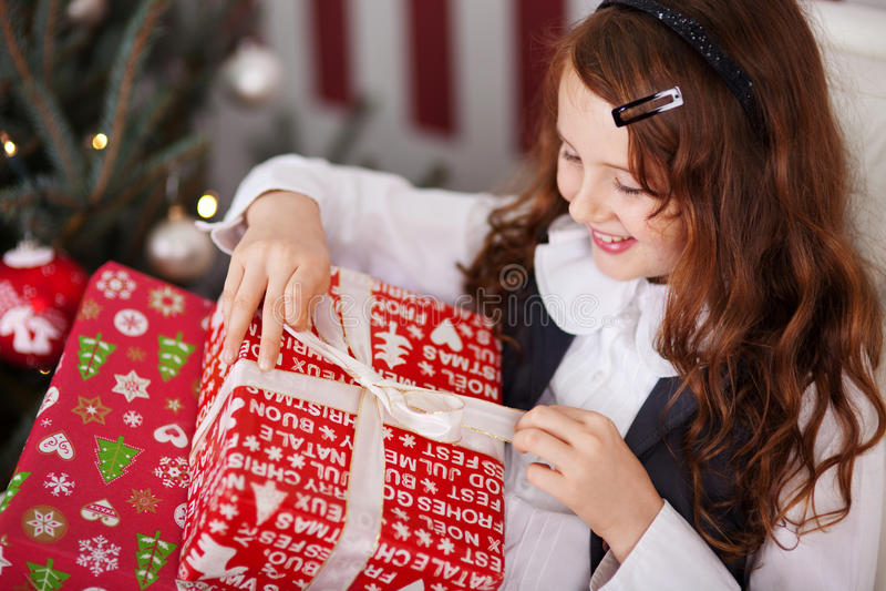 Opgewekt meisje dat haar aanwezige Kerstmis ongedaan maakt royalty-vrije stock fotografie