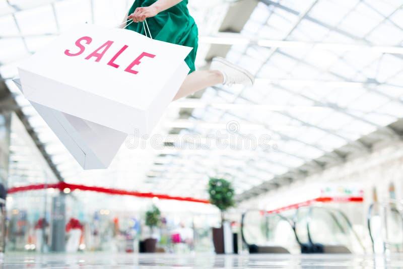 Opgewekt meisje die met het winkelen zak springen stock fotografie