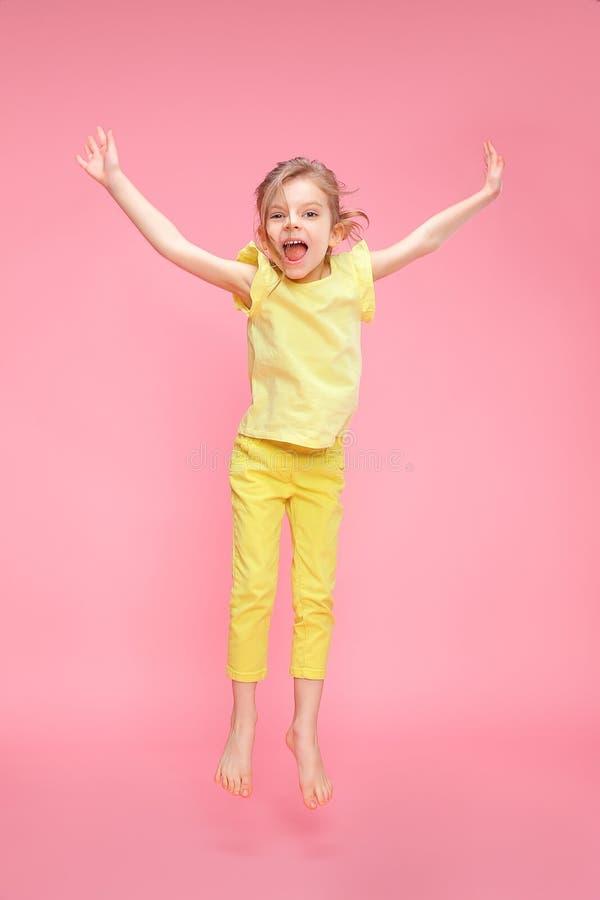 Opgewekt meisje die in studio springen stock afbeelding