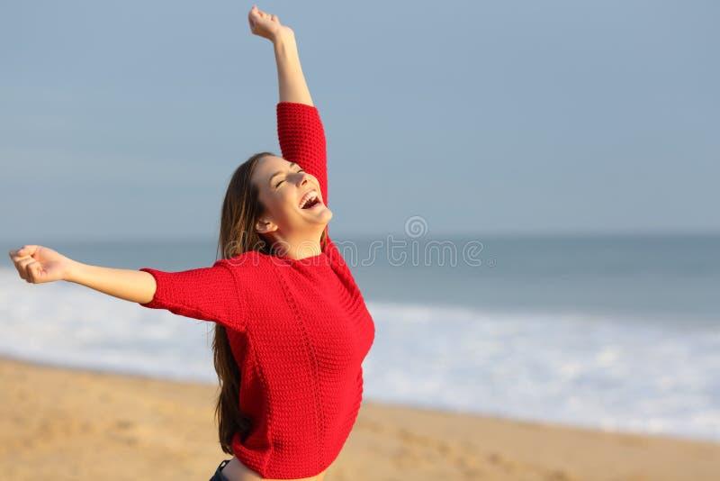 Opgewekt meisje in rood op een strand die wapens opheffen stock fotografie