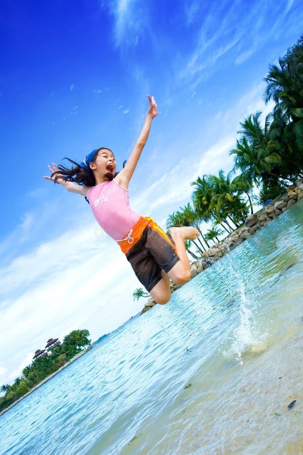 Opgewekt meisje, springend op het lagunestrand stock foto