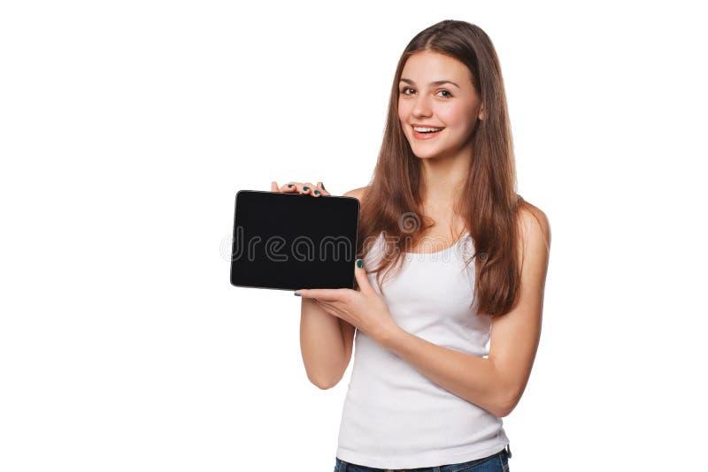 Opgewekt meisje in wit overhemd die de monitor van tabletpc tonen Glimlachende die vrouw met tabletpc, op oranje achtergrond word royalty-vrije stock afbeeldingen