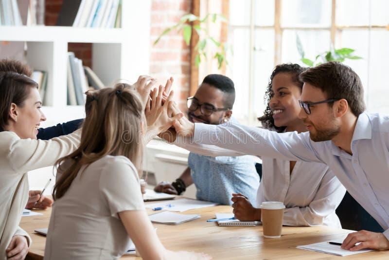 Opgewekt multiraciaal team die hoogte vijf geven op bedrijfvergadering royalty-vrije stock foto's