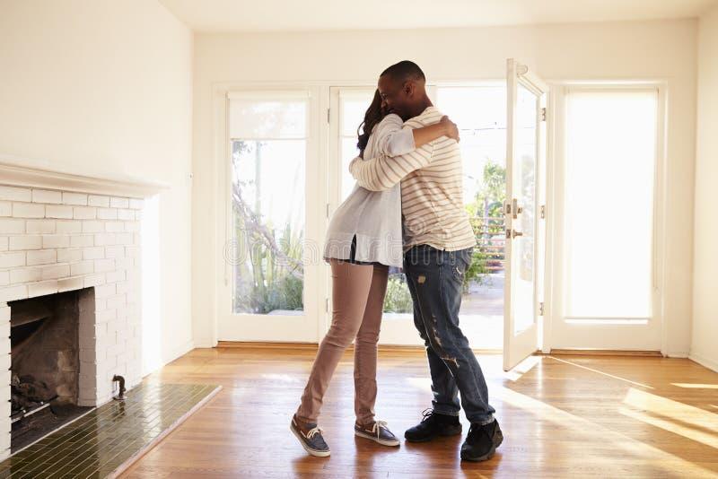 Opgewekt Paar die in Nieuw Huis bij het Bewegen van Dag koesteren stock afbeeldingen