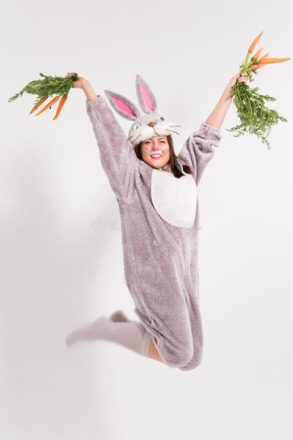 Opgewekt springend konijntjesmeisje met wortelen royalty-vrije stock fotografie