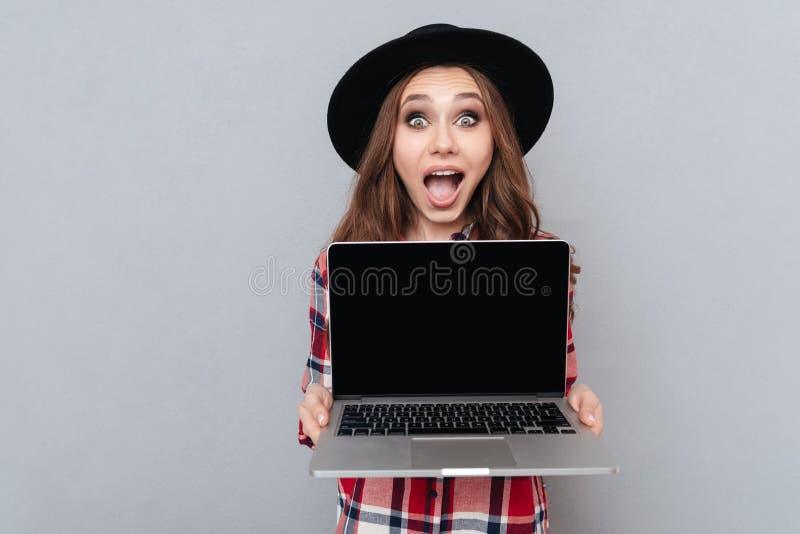 Opgewekt toevallig meisje in laptop van het de holdings lege scherm van het plaidoverhemd royalty-vrije stock foto's