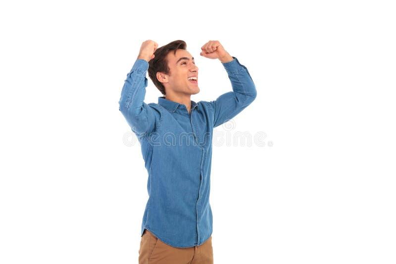 Opgewekt toevallig mens het vieren succes met omhoog handen stock afbeeldingen