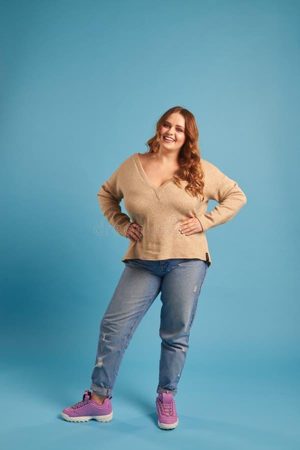 Opgewekt vettig meisje in jeans en sweatshirt die haar handen houden royalty-vrije stock afbeelding