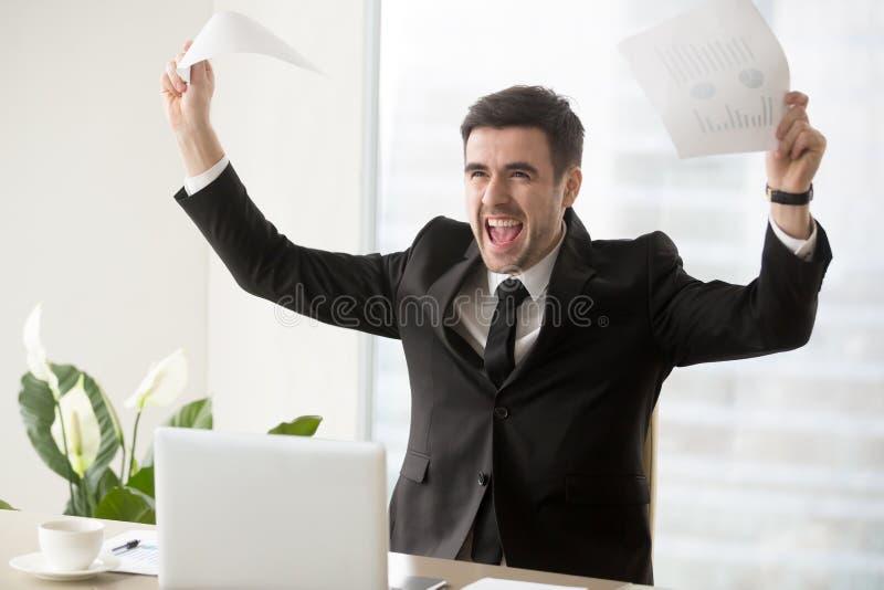 Opgewekt zakenman het vieren bedrijfssucces, die documenten houden stock afbeeldingen